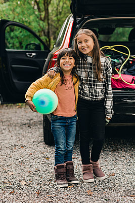 Portrait of smiling sisters standing against electric car - p426m2194941 by Maskot