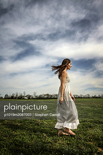 Young woman in a meadow - p1019m2087003 by Stephen Carroll