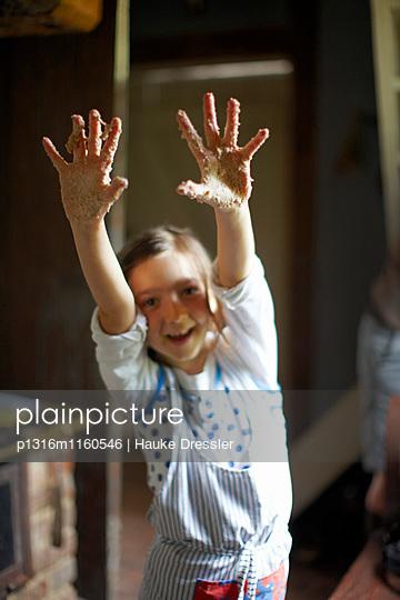 Mädchen mit Teig verklebten Händen, Haus Strauss, Bauernkate in Klein Thurow, Roggendorf, Mecklenburg-Vorpommern, Deutschland - p1316m1160546 von Hauke Dressler