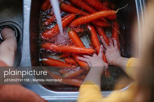 Girl washing carrots in kitchen sink - p312m2191158 by Matilda Holmqvist