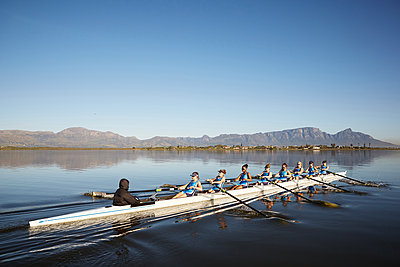 Female rowers rowing scull on sunny lake under blue sky - p1023m1575840 by Richard Johnson