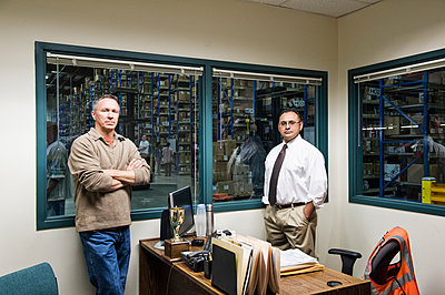 Team portrait of a male Hispanic American executive and a male Caucasian factory worker in an office in the middle of a large distribution warehouse full of racks of products stored in cardboard boxes on pallets. - p1100m1575497 by Mint Images