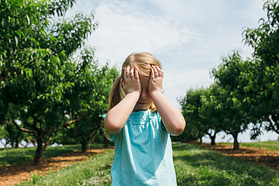 Blonde girl covering eyes with hands - p1238m1461803 by Amanda Voelker
