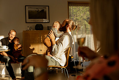 Fathers with their babies resting in living room - p312m2280474 by Lisa Öberg