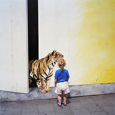 Belgium, Brussels - Rear view of a girl standing on the street and looking at a painted tiger on a wall - p3485181 by Nina Korhonen