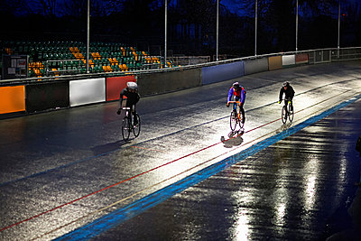 Young adult cyclists racing on velodrome track - p429m928887f by Dark Horse