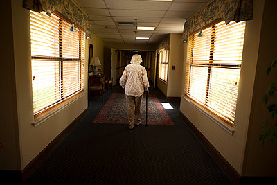 Older Caucasian woman walking with cane in retirement home - p555m1408820 by Shestock