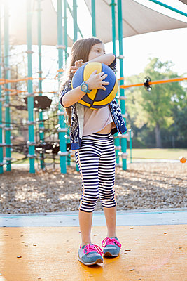 Girl holding basketball in playground - p924m1493719 by Kinzie Riehm