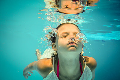 Girl diving in pool - p1019m1461896 by Stephen Carroll