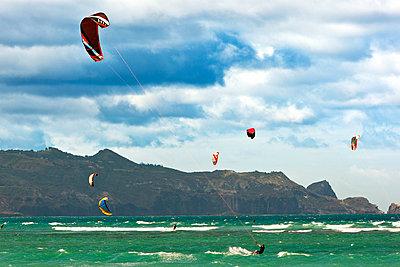Man kiteboarding in sea against cloudy sky - p1166m979835f by Cavan Images
