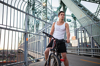 Young man running on bike path in urban city setting at sunset - p1362m2163553 by Charles Knox