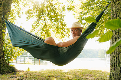 Senior man wearing straw hat relaxing in hammock at lakeshore - p300m2080224 by Gustafsson
