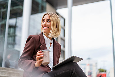 Smiling young businesswoman with tablet and coffee to go in the city - p300m2143489 by Daniel Ingold