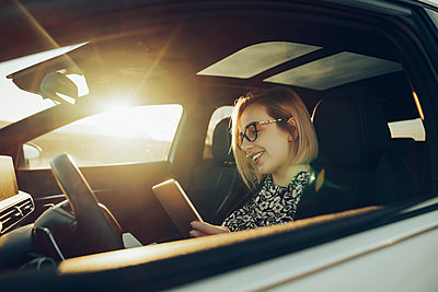 Young blond woman using smartphone in the car - p300m2160247 by Mikel Taboada