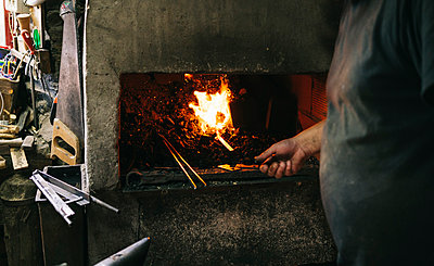 Close-up of blacksmith working at forge in his workshop - p300m2180320 by Daniel González