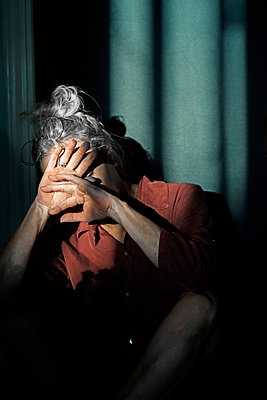 Senior woman shielding eyes while sitting against wall at home - p300m2206696 by Eloisa Ramos