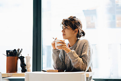Thoughtful woman looking away while sitting with coffee cup at table in cafeteria - p426m2194983 by Maskot