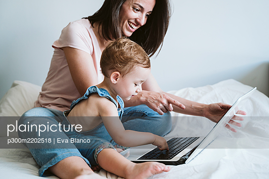 Mother and baby girl using laptop on bed at home - p300m2202518 by Eva Blanco