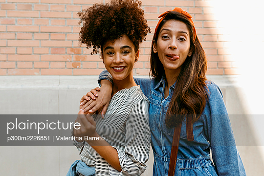 Young woman sticking tongue out while standing with friend against wall - p300m2226851 by Valentina Barreto