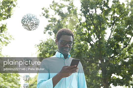 Mature man text messaging on smart phone while listening to music through earphones standing in park - p300m2227146 by Pete Muller