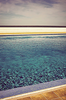 Looking across swimming pool to sea horizon - p1047m789493 by Sally Mundy