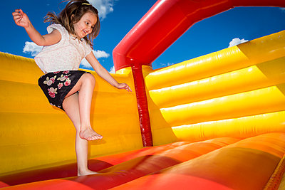 Girl jumping in bouncy castle - p1418m2013874 by Jan Håkan Dahlström
