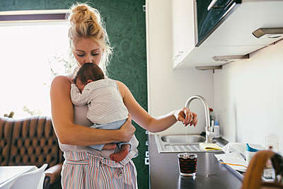 Mother holding newborn baby in kitchen while making tea - p300m2042739 by Mareen Fischinger