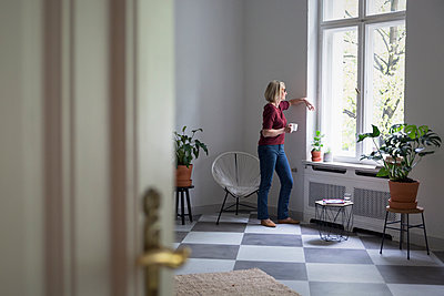 Mature woman at home looking out of window - p300m2069457 by Rainer Berg