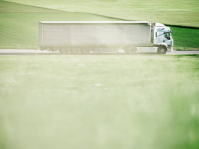 Truck moving on highway along green field - p300m2131771 by Christian Vorhofer