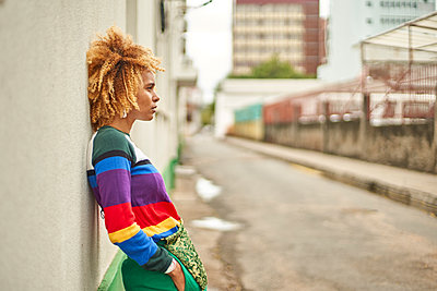 Portrait of a young woman in an afro hairstyle leaning on a wall in the city - p300m2170788 by Veam