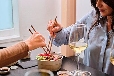 Female customer having food with chopsticks at restaurant - p300m2264754 by Antonio Ovejero Diaz
