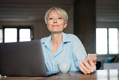 Smiling freelance worker with laptop looking away while holding mobile phone at desk in home office - p300m2267791 by Robijn Page