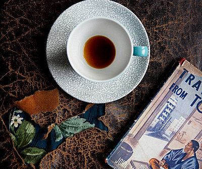 Elevated view of cup and saucer with hardback book on leather ripped surface - p349m789743 by Brent Darby