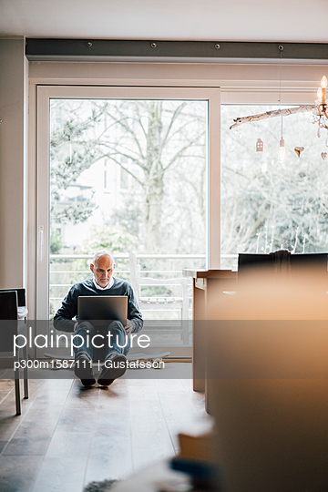 Senior man sitting on ground, using laptop - p300m1587111 von Gustafsson