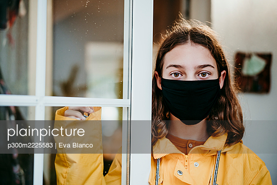 Girl wearing raincoat and face mask standing by door at home - p300m2225583 by Eva Blanco