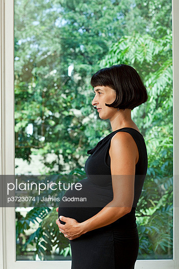 Profile view of pregnant woman in black dress - p3723074 by James Godman