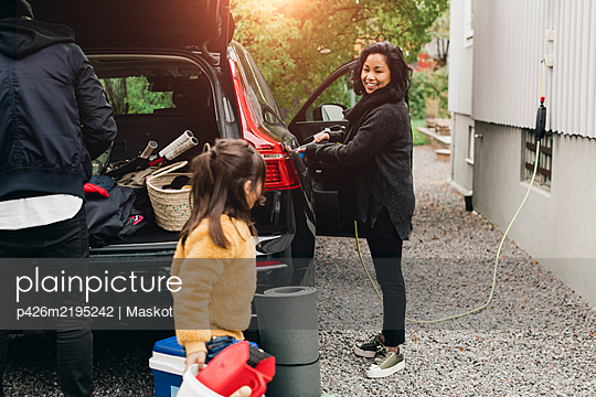 Smiling woman charging car while family loading luggage in trunk - p426m2195242 by Maskot