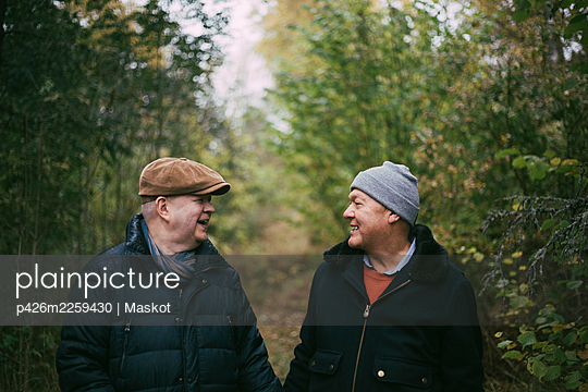 Smiling senior gay couple looking at each other in forest - p426m2259430 by Maskot