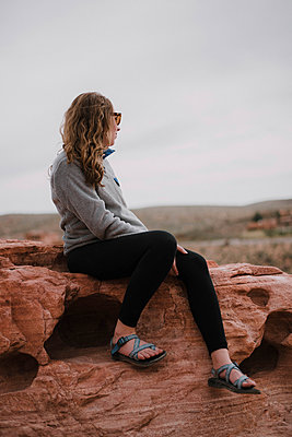 Full length of woman sitting on rocks against sky at Red Rock Canyon National Conservation Area - p1166m1417486 by Cavan Images