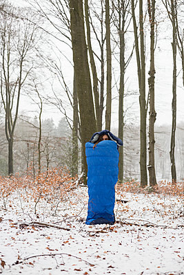 Girl standing in a sleeping bag in the snow - p1621m2231955 by Anke Doerschlen