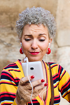 Portrait of pierced mature woman with grey curly hair looking at cell phone - p300m2132421 by Retales Botijero