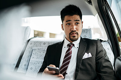 Young businessman with cell phone in a taxi - p300m2140131 by Juri Pozzi