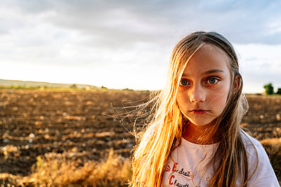 Pre-adolescent girl with long blond hair standing against sky during sunset - p300m2202720 by Jose Luis CARRASCOSA