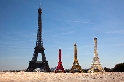 Three Eiffel Tower replica souvenirs next to the real Eiffel Tower, focus on foreground  - p30118837f by Paul Hudson
