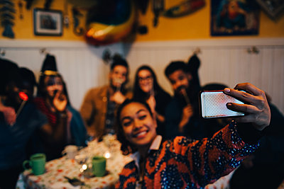 Smiling young woman taking selfie with multi-ethnic friends holding props while sitting at restaurant during dinner part - p426m2046278 by Maskot