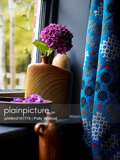 PInk hydrangeas in wooden vase on windowsill with blue curtain fabric - p349m2167774 by Polly Wreford