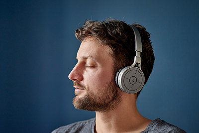 Young man listens to music with headphones - p1124m1589440 by Willing-Holtz