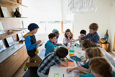 Boys and girls conducting science experiment dining table - p1192m1129571f by Hero Images