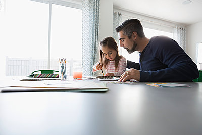 Father and daughter painting at dining room table - p1192m1201959 by Hero Images