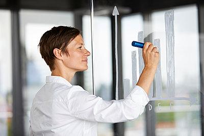 Businesswoman drawing bar chart at glass pane in office - p300m2012974 von Rainer Berg